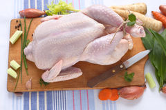 Raw chicken. Whole raw chicken on a cutting board and vegetables Stock Photo