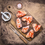 Raw chicken wings with barbecue sauce and pepper, fork for meat on a cutting board wooden rustic background top view close up Stock Photography