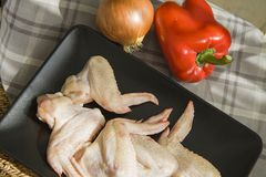 Raw chicken wings on black with onion and red paprika Royalty Free Stock Photography