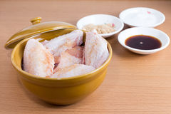 Raw chicken wings in bowl on wooden table. Stock Photos