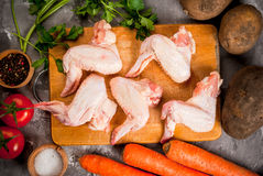 Raw chicken wings on chopping board Stock Images
