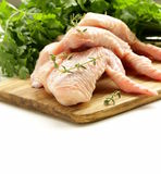 Raw chicken wings on chopping board. With herbs Stock Photography