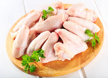 Raw chicken wings. On chopping board with parsley Stock Images