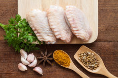 Raw chicken wings on chopping board. With spices Stock Photography