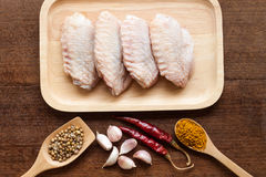 Raw chicken wings on chopping board. With spices Royalty Free Stock Images