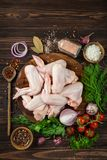 Raw chicken wings on cutting board with spices and herbs. On wooden background, top view Royalty Free Stock Photo
