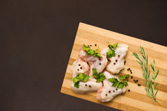 Raw chicken wings on cutting board with spices and rosemary. Raw chicken wings on a cutting board with spices and rosemary Royalty Free Stock Images