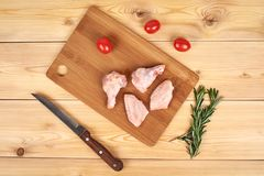 Raw chicken wings on cutting board, wooden background.  Stock Image
