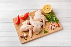 Raw chicken wings in marinade with sauce, pepper and greens on wooden stand. Selective focus stock photo