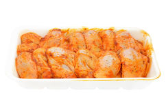Raw chicken wings marinated. In a container isolated on white background Royalty Free Stock Image