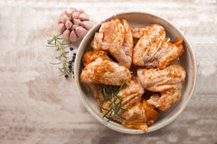 Raw chicken wings. Marinated with garlic and herbs on wood background Stock Photos