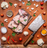 Raw chicken wings with parsley on a cutting board Meat cleaver sharp red pepper cauliflower mushrooms seasoning tomatoes on rustic. Raw chicken wings with Stock Images