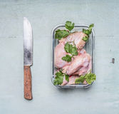 Raw chicken wings with parsley in a transparent bowl with a kitchen knife on rusti? wooden background  top view close up. Raw chicken wings with parsley a Royalty Free Stock Images