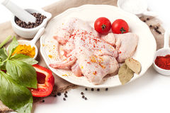 Raw chicken wings. Plate of raw chicken wings with spices and vegetables over white Stock Photography