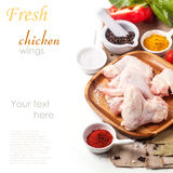 Raw chicken wings. Plate of raw chicken wings with spices and vegetables over white with sample text. See series Royalty Free Stock Photo