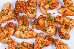 Raw chicken wings  prepared for roast. Raw juicy chicken wings marinated with honey, soy sauce, spices and sprinkled with finely chopped parsley on white Stock Photo