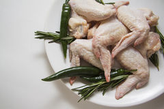 Raw chicken wings with rosemary. And green chili peppers Stock Photo