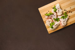 Raw chicken wings with spices on a cutting board. And a dark countertop. Tpo view Royalty Free Stock Photography