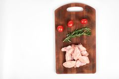 Raw chicken wings on a cutting board isolated on white background. Raw chicken wings, tomatoes and rosemary on a cutting board isolated on white background Royalty Free Stock Photos
