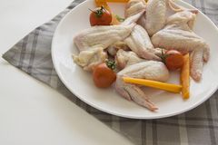 Raw chicken wings with vegetables on grey tablecloth. Closeup of plate with raw chicken wings. copy space for text Stock Images