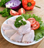 Raw chicken wings with vegetables. On wooden board Royalty Free Stock Photos