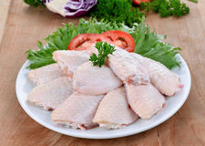 Raw chicken wings with vegetables. On wooden board Royalty Free Stock Image