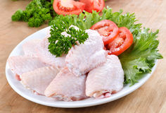 Raw chicken wings with vegetables. On wooden board Stock Photography