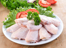 Raw chicken wings with vegetables. On wooden board Stock Photos
