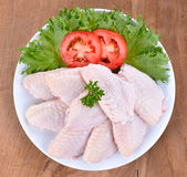 Raw chicken wings. With vegetables on wooden board Royalty Free Stock Image
