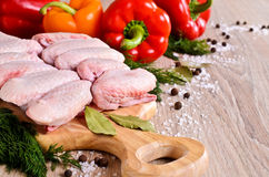 Raw chicken wings. On a wooden Board on the background of paprika and spices Stock Photo
