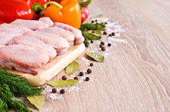 Raw chicken wings. On a wooden Board on the background of paprika and spices Stock Photos