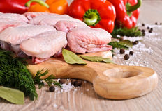 Raw chicken wings. On a wooden Board on the background of paprika and spices Royalty Free Stock Photos