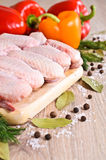 Raw chicken wings. On a wooden Board on the background of paprika and spices Royalty Free Stock Images