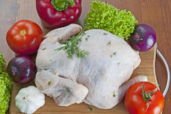 Raw chicken. On wooden board with vegetables Stock Photos