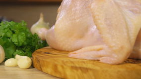 Raw chicken on a wooden cutting board sprinkled with spices stock footage