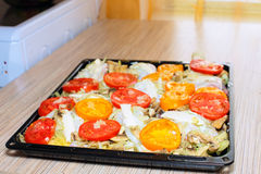 Raw chiken on baking tray with tomato Royalty Free Stock Photography