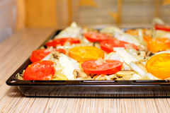 Raw chiken on baking tray with tomato and potato Royalty Free Stock Image
