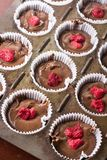 Raw chocolate muffin pastry dough with raspberry ready for baking.  Stock Photos