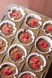 Raw chocolate muffin pastry dough with raspberry ready for baking.  Royalty Free Stock Photo