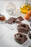 Raw chocolate pasta. Raw unprepared chocolate pasta noodles, with ingredients for cooking - chocolate, cocoa, flour, eggs,  oil. On a white kitchen marble table Stock Photo