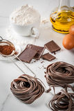 Raw chocolate pasta. Raw unprepared chocolate pasta noodles, with ingredients for cooking - chocolate, cocoa, flour, eggs,  oil. On a white kitchen marble table Royalty Free Stock Photos