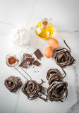 Raw chocolate pasta. Raw unprepared chocolate pasta noodles, with ingredients for cooking - chocolate, cocoa, flour, eggs,  oil. On a white kitchen marble table Stock Photography