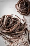 Raw chocolate pasta. Raw unprepared chocolate pasta noodles. On a white kitchen marble table. Copy space Royalty Free Stock Image