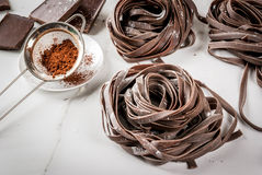 Raw chocolate pasta. Raw unprepared chocolate pasta noodles. On a white kitchen marble table. Copy space Royalty Free Stock Photo
