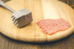 Raw chop on a cutting wooden board. Raw chop and steel hammer on a cutting board Stock Photography