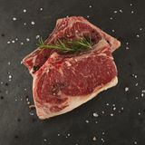 Raw chop meat on a slate plate. Rustical bbq with pepper and rosemary Royalty Free Stock Images