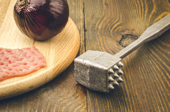 Raw chop, steel hammer and onions on a table. Raw chop and onions on a cutting board Stock Image