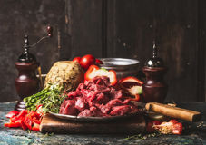 Raw chopped Beef goulash  of young bulls with vegetables and cooking ingredients on dark rustic kitchen table. Preparation Stock Photo