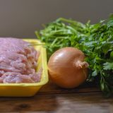 Raw chopped chicken meat, fresh parsley and onion. stock photos