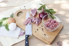 Raw chopped pork tenderloin with herbs in a glass bowl on a wooden board Royalty Free Stock Photos